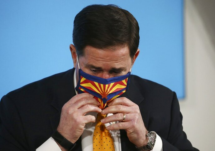 Arizona Republican Gov. Doug Ducey puts a face-covering back on after speaking about the latest coronavirus data at a news conference Thursday, June 25, 2020, in Phoenix. (AP Photo/Ross D. Franklin, Pool)