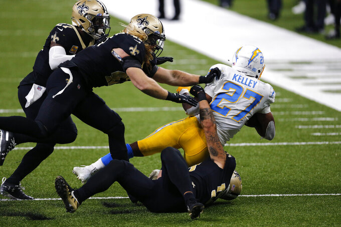 Los Angeles Chargers running back Joshua Kelley (27) is brought down by New Orleans Saints linebacker Zack Baun, on ground, middle linebacker Alex Anzalone, center, and strong safety Malcolm Jenkins in the second half of an NFL football game in New Orleans, Monday, Oct. 12, 2020. (AP Photo/Brett Duke)
