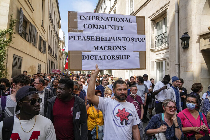 Anti-vaccine protester holds a placard during a rally in Paris, Saturday, July 17, 2021. Tens of thousands of people protested across France on Saturday against the government's latest measures to curb rising COVID-19 infections and drive up vaccinations in the country. (AP Photo/Michel Euler)