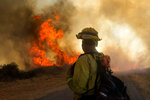 A firefighter watches the Apple Fire in Cherry Valley, Calif., Saturday, Aug. 1, 2020. A wildfire northwest of Palm Springs flared up Saturday afternoon, prompting authorities to issue new evacuation orders as firefighters fought the blaze in triple-degree heat. (AP Photo/Ringo H.W. Chiu)