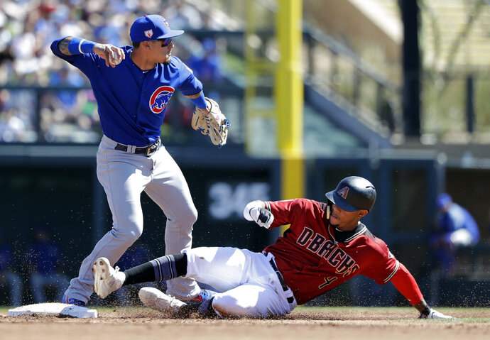 Chicago Cubs shortstop Javier Baez, left, throws to first base after forcing out Arizona Diamondbacks' Ketel Marte at second base in the first inning of a spring training baseball game Saturday, March 16, 2019, in Scottsdale, Ariz. Baez completed the double play on Diamondbacks' Carson Kelly at first. (AP Photo/Elaine Thompson)