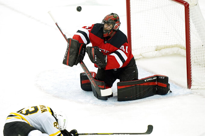 Boston Bruins center Karson Kuhlman (83) ducks as New Jersey Devils goaltender Scott Wedgewood (41) makes a save during the first period of an NHL hockey game, Monday, May 3, 2021, in Newark, N.J. (AP Photo/Kathy Willens)