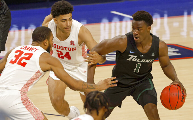 Tulane guard Sion James (1) handles the ball as Houston guard Quentin Grimes (24) and forward Reggie Chaney (32) defend during the second half of an NCAA college basketball game in the quarterfinal round of the American Athletic Conference men's tournament Friday, March 12, 2021, in Fort Worth, Texas. (AP Photo/Ron Jenkins)