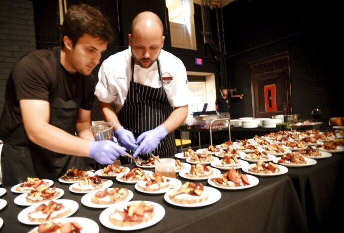 In this Aug. 4, 2019 photo, Chef Anthony and Amanda Felan's Second Act Supper Club prepares for a dinner on the stage at the Shreveport Municipal Auditorium in Shreveport, La. Anthony Felan learned an invaluable lesson after graduating from Le Cordon Bleu culinary institute and working on the ground-level of San Francisco's dining scene: If you're not invited to the exclusive, secret dinner parties, throw your own.  (Henrietta Wildsmith/The Shreveport Times via AP)