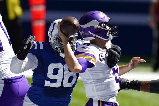 Minnesota Vikings quarterback Kirk Cousins, right, is pressured by dIndianapolis Colts' Denico Autry (96) during the first half of an NFL football game, Sunday, Sept. 20, 2020, in Indianapolis. (AP Photo/Michael Conroy)