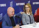FILE- In this Oct. 2, 2018, file photo retired NASA astronaut and Navy Capt. Mark Kelly speaks as his wife, former U.S. Rep. Gabby Giffords looks on during a roundtable discussion with gun violence survivors, at UNLV in Las Vegas. Kelly said Tuesday, Feb. 12, 2019, that he's running to finish John McCain's term in the U.S. Senate. (Bizuayehu Tesfaye/Las Vegas Review-Journal via AP, File)