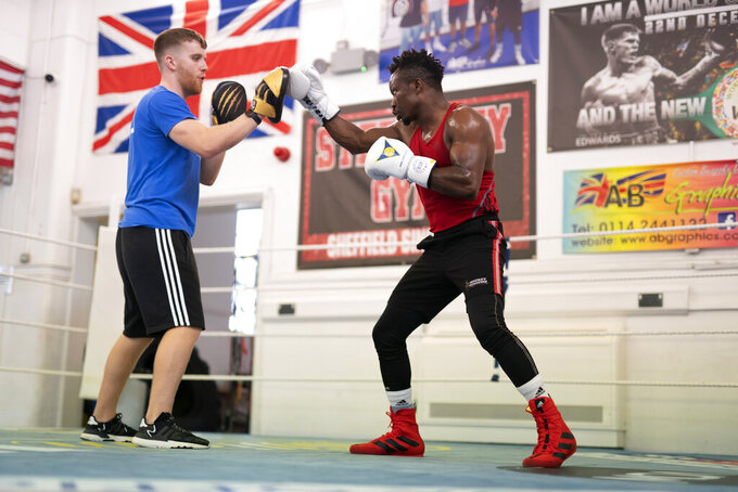 Boxer Thomas Essomba trains with boxing coach Pearce Gudgeon at Steel City Gym in Sheffield, England, Thursday, Aug. 4, 2021. Cameroonian boxer Thomas Essomba, was one of seven people who defected at London 2012. Nine years on, he talks to AP about what it's been like to live with that decision. (AP Photo/Jon Super)