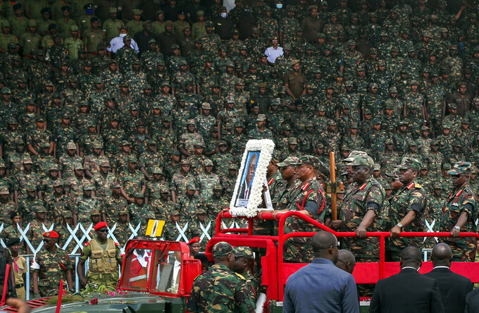 Members of the military parade with a portrait of former president John Magufuli as his body lies in state at Uhuru stadium in Dar es Salaam, Tanzania Saturday, March 20, 2021. Magufuli, a prominent COVID-19 skeptic whose populist rule often cast his country in a harsh international spotlight, died Wednesday aged 61 of heart failure, it was announced by Vice President Samia Suluhu Hassan, who was sworn-in as the country's new president on Friday. (AP Photo)