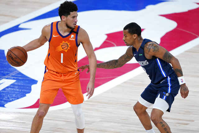 Phoenix Suns' Devin Booker (1) dribbles as Dallas Mavericks' Trey Burke defends during the second half of an NBA basketball game Thursday, Aug. 13, 2020 in Lake Buena Vista, Fla. (AP Photo/Ashley Landis, Pool)