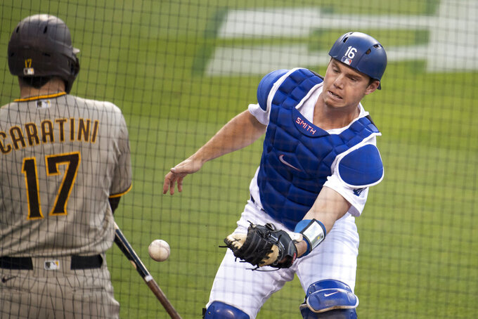 Los Angeles Dodgers catcher Will Smith, right, loses a popup during the second inning of a baseball game against the San Diego Padres in Los Angeles, Saturday, April 24, 2021. (AP Photo/Kyusung Gong)