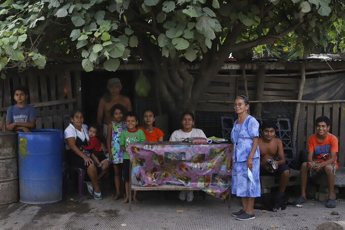 Members of the Orellana family pose for a photo outside their home in Los Angelitos, El Salvador, Wednesday, July 28, 2021. The Orellana family is among the residents of Los Angelitos who did not receive an invitation from the president to receive a new home in the residential development Ciudad Marsella. Their shack of wood pallets and aluminum sheeting held up during the October 2020 tropical storm that devastated their community, but they are awaiting the next hurricane season with fear. (AP Photo/Salvador Melendez)