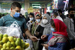 People wear protective face masks to help prevent the spread of the coronavirus in the Tajrish traditional bazaar in northern Tehran, Iran, Thursday, Oct. 15, 2020. Eight months after the pandemic first stormed Iran, pummeling its already weakened economy and sickening officials at the highest levels of its government, authorities appear just as helpless to prevent its spread. (AP Photo/Ebrahim Noroozi)