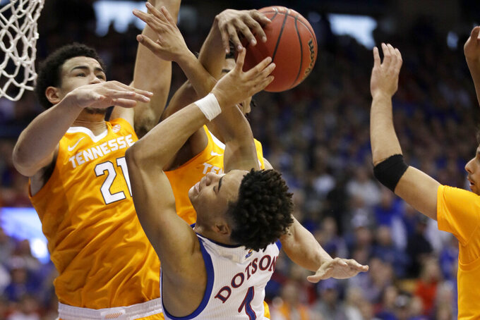 Tennessee guard Jalen Johnson, back, and forward Olivier Nkamhoua (21) block a shot by Kansas guard Devon Dotson (1) during the first half of an NCAA college basketball game in Lawrence, Kan., Saturday, Jan. 25, 2020. (AP Photo/Orlin Wagner)