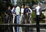 President Donald Trump waves as he visits a neighborhood impacted by Hurricane Florence, Wednesday, Sept. 19, 2018, in Conway, S.C., with South Carolina Gov. Henry McMaster, third from right. (AP Photo/Evan Vucci)