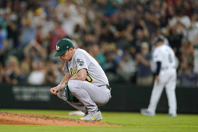 Oakland Athletics starting pitcher Chris Bassitt crouches by the mound after he gave up a two-run home run to Seattle Mariners' Mitch Haniger during the fifth inning of a baseball game Saturday, July 24, 2021, in Seattle. (AP Photo/Ted S. Warren)