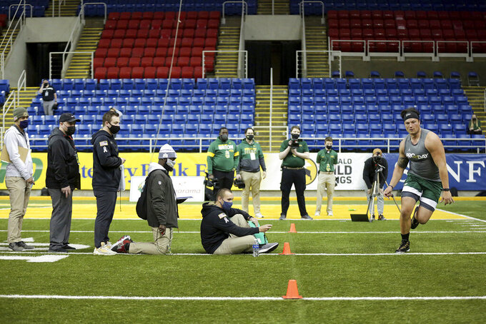 NFL scouts watch as North Dakota State lineman Dillon Radunz does drills at the school's football NFL Pro Day Friday, March, 12, 2021, in Fargo, North Dakota. (AP Photo/Andy Clayton- King)