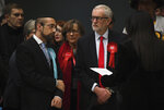 British opposition Labour Party leader Jeremy Corbyn, right,  waits for the declaration of his seat in the 2019 general election in Islington, London, Friday, Dec. 13, 2019. The first handful of results to be declared in Britain's election are showing a surge in support for to the Conservatives in northern England seats where Labour has long been dominant. (AP Photo/Alberto Pezzali)
