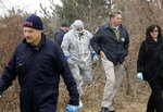 FILE - In this April 11, 2011, file photo, emergency personnel search through the brush for human remains near Jones Beach in Wantagh, N.Y. On Friday, May 22, 2020, authorities investigating the long-running mystery of skeletal remains strewn along a suburban New York beach highway said they have identified the remains of one of the women using DNA technology. (AP Photo/Seth Wenig, File)
