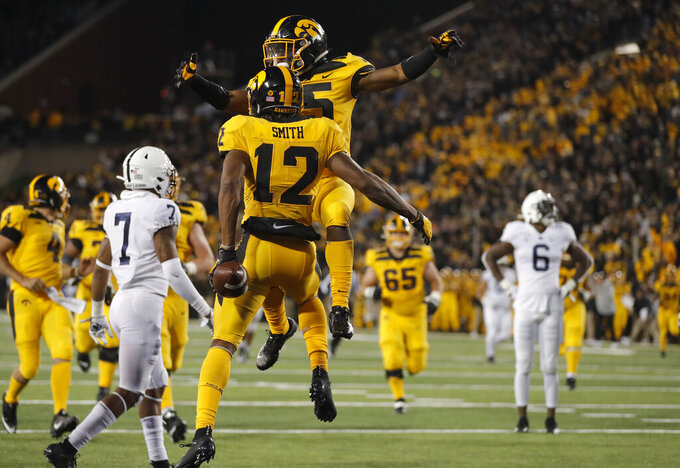 Iowa running back Tyler Goodson, top, congratulates wide receiver Brandon Smith on his touchdown during the second half of an NCAA college football game against Penn State, Saturday, Oct. 12, 2019, in Iowa City, Iowa. Penn State won 17-12. (AP Photo/Matthew Putney)
