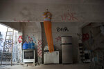 A half torso mannequin decorated with an orange veil hangs from a beam backdropped by donated items in the courtyard of the squat known as Casa Nem, occupied by members of the LGBTQ community who are in self-quarantine as a protective measure against the new coronavirus, in Rio de Janeiro, Brazil, Wednesday, July 8, 2020. They receive food donations as well and are barred from leaving unless facing medical emergency or other exceptional circumstances. (AP Photo/Silvia Izquierdo)