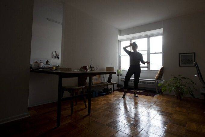 """In this Thursday, April 23, 2020, photo dancers and choreographer Netta Yerushalmy warms up during a zoom dance rehearsal in her living room on the Lower East Side neighborhood of New York. Yerushalmy has built a career in movement and community but since the coronavirus pandemic both are gone now. Many artists like Yerushalmy have turned to social media to get their work out, posting music and artwork on Instagram. """"We're trying to figure out what are the things that preserve that sense that we're all here now together doing something together,"""" she said.  (AP Photo/Mary Altaffer)"""