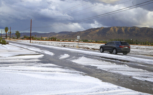 A vehicle travels along a street after several inches of hail fell Thursday, Nov. 21, 2019, in Laveen, Ariz. (AP Photo/Ross D. Franklin)