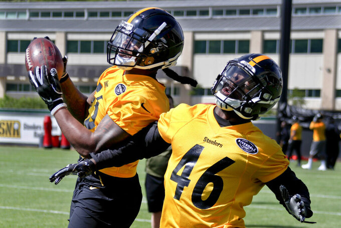FILE - In this May 11, 2019, file photo, Pittsburgh Steelers linebacker Devin Bush, left, catches the ball during pass defense drills at NFL football practice in Pittsburgh. First-round pick Bush will get a chance to show his eye-opening debut _ when the inside linebacker made 10 tackles against Tampa Bay _ was a taste of things to come. (AP Photo/Keith Srakocic, File)