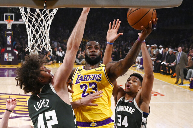 Los Angeles Lakers forward LeBron James, center, shoots as Milwaukee Bucks center Robin Lopez, left, and forward Giannis Antetokounmpo defend during the first half of an NBA basketball game Friday, March 6, 2020, in Los Angeles. (AP Photo/Mark J. Terrill)