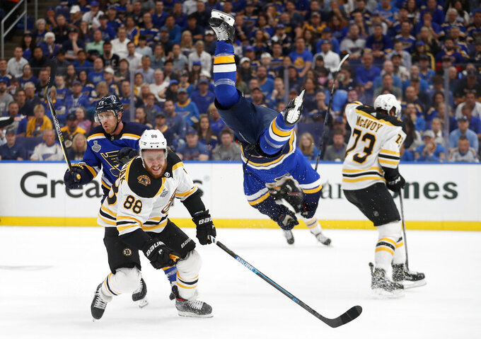St. Louis Blues center Brayden Schenn, second from right, flips past Boston Bruins right wing David Pastrnak (88), of the Czech Republic, during the first period of Game 3 of the NHL hockey Stanley Cup Final Saturday, June 1, 2019, in St. Louis. (AP Photo/Jeff Roberson)