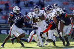 Texas A&M running back Isaiah Spiller (28) carries the ball as Auburn defensive back Smoke Monday (21) and defensive back Jamien Sherwood (20) tackle him during the second half of an NCAA college football game on Saturday, Dec. 5, 2020, in Auburn, Ala.  (AP Photo/Butch Dill)
