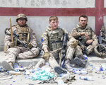 In this photo provided by the Ministry of Defence, members of the British and US, left) military engaged in the evacuation of people out of Kabul, Afghanistan take a brief rest from their duties on Friday, Aug. 20, 2021. (Ministry of Defence via AP)