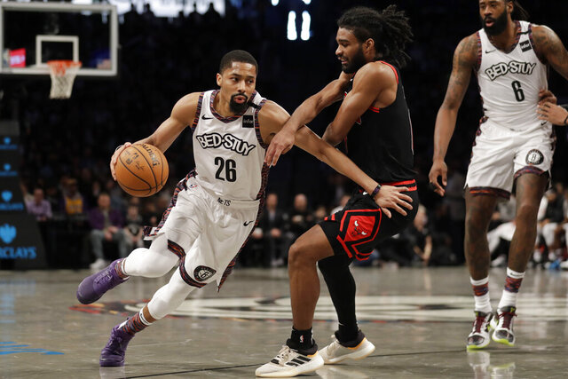 FILE - In this  Sunday, March 8, 2020 file photo, Brooklyn Nets' Spencer Dinwiddie (26) drives to the basket around Chicago Bulls' Coby White during the second half of an NBA basketball game at the Barclays Center in New York. Kevin Durant and Kyrie Irving aren't coming back, DeAndre Jordan and Wilson Chandler aren't going to Florida, and Spencer Dinwiddie's status is unclear after he and Jordan tested positive for the coronavirus. The Brooklyn Nets don't have much of a team left, but general manager Sean Marks says they never considered not restarting the season later this month. (AP Photo/Seth Wenig, File)