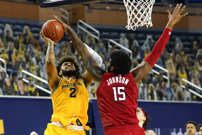 Rutgers center Myles Johnson (15) blocks a Michigan Wolverines forward Isaiah Livers (2) shot in the second half of an NCAA college basketball game in Ann Arbor, Mich., Thursday, Feb. 18, 2021. (AP Photo/Paul Sancya)