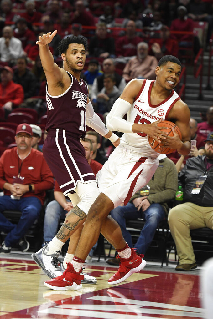Arkansas guard Mason Jones (13) calls a timeout in front of Mississippi State defender Quinndary Weatherspoon during the first half of an NCAA college basketball game Saturday, Feb. 16, 2019, in Fayetteville, Ark. (AP Photo/Michael Woods)