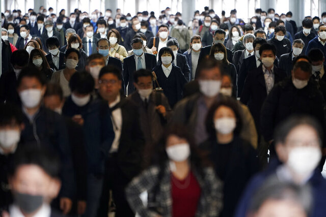 A station passageway is crowded with commuters wearing face mask during a rush hour in Tokyo Monday, April 27, 2020. Japan's Prime Minister Shinzo Abe expanded a state of emergency to all of Japan from just Tokyo and other urban areas as the virus continues to spread. (AP Photo/Eugene Hoshiko)