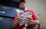 In this Oct. 8, 2019 photo, gas attendant Orlando Godoy counts his Bolivars bills in San Antonio de los Altos on the outskirts of Caracas, Venezuela, a country where a full tank these days costs a tiny fraction of a U.S. penny. The smallest bill in circulation, 50 bolivars, is worth about quarter of a U.S. penny, and the largest bill, 50,000 bolivars, equals $2.50 dollars. (AP Photo/Ariana Cubillos)