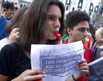 An opposition demonstrator holds an anti-Russia poster as other gather in front of the Georgian Parliament building in Tbilisi, Georgia, Monday, June 24, 2019. Demonstrators have returned to parliament for daily rallies, demanding the release of detained protesters, the ouster of the nation's interior minister and changes in the electoral law to have legislators chosen fully proportionally rather than the current mix of party-list and single-mandate representatives. (AP Photo/Shakh Aivazov)