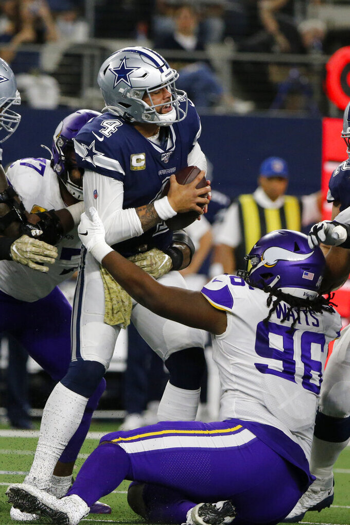 Dallas Cowboys quarterback Dak Prescott (4) is sacked by Minnesota Vikings' Armon Watts (96) and others during the first half of an NFL football game in Arlington, Texas, Sunday, Nov. 10, 2019. (AP Photo/Michael Ainsworth)