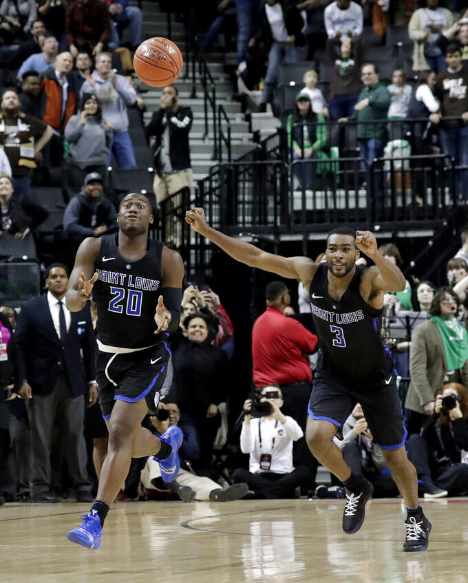 Saint Louis guards Fred Thatch Jr. (20) and Javon Bess (3) react moments after the team's win over St. Bonaventure during an NCAA college basketball game in the final of the Atlantic 10 men's tournament, Sunday, March 17, 2019, in New York. Saint Louis won 55-53. (AP Photo/Julio Cortez)