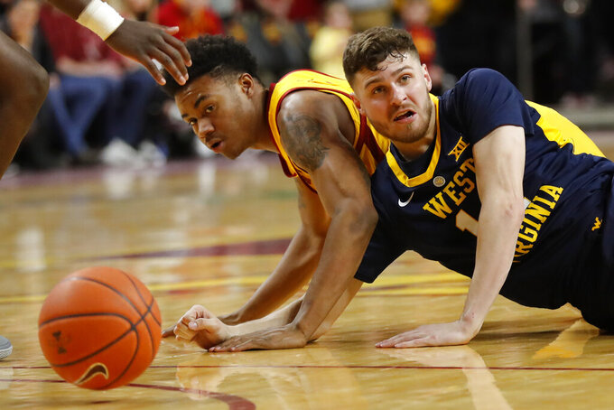 West Virginia guard Chase Harler and Iowa State forward Zion Griffin, left, go to the court while chasing the ball during the second half of an NCAA college basketball game Wednesday, Jan. 30, 2019, in Ames, Iowa. Iowa State won 93-68. (AP Photo/Charlie Neibergall)