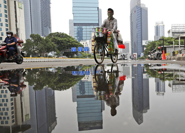 A drink vendor rides his bicycle reflected in a puddle in the main business district in Jakarta, Indonesia, Thursday, Nov. 5, 2020. Indonesia's economy entered its first recession since the Asian financial crisis more than two decades ago as the country struggles to curb the coronavirus pandemic under control. (AP Photo/Dita Alangkara)