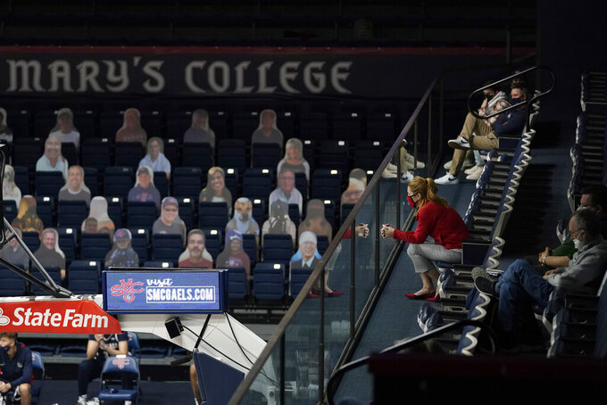 Fans sit socially distanced at right, as cutouts are in seats at left during the second half of an NCAA college basketball game between Saint Mary's and Gonzaga in Moraga, Calif., Saturday, Jan. 16, 2021. (AP Photo/Jeff Chiu)