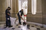 Workmen clean up debris outside the office of Speaker of the House Nancy Pelosi on the day after violent protesters loyal to President Donald Trump stormed the U.S. Congress, at the Capitol in Washington, Thursday, Jan. 7, 2021. (AP Photo/J. Scott Applewhite)