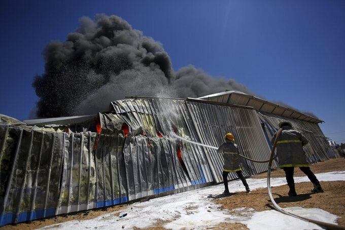 Palestinian firefighters work to extinguish a fire at a paint factory after it was hit by an Israeli airstrike, in Rafah, Gaza Strip, Tuesday, May 18, 2021. (AP Photo/Yousef Masoud)