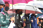 Drivers stand under umbrellas prior to the Formula One Grand Prix at the Spa-Francorchamps racetrack in Spa, Belgium, Sunday, Aug. 29, 2021. (John Thys, Pool Photo via AP)