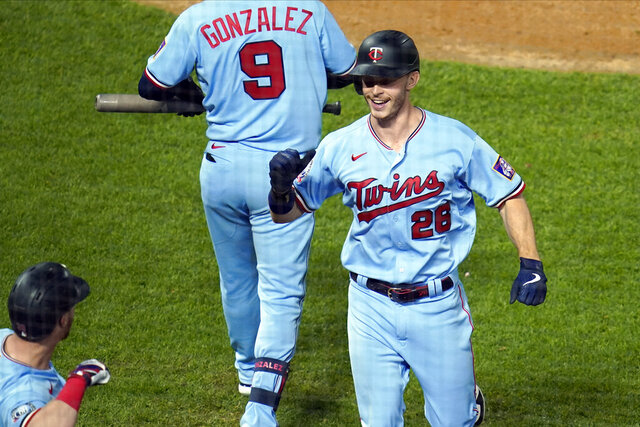 Minnesota Twins' Max Kepler, right, smiles as he scores on a solo home run to tie the baseball game in the eighth inning Tuesday, Sept. 22, 2020, in Minneapolis. (AP Photo/Jim Mone)
