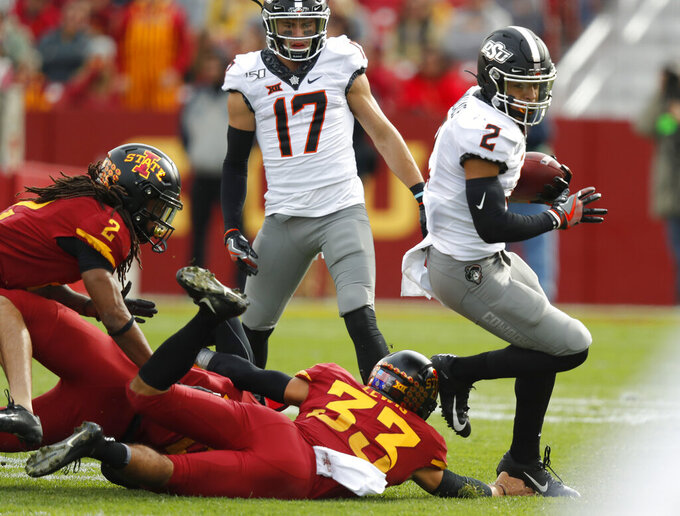 Oklahoma State wide receiver Tylan Wallace, right, breaks free from Iowa State defensive back Braxton Lewis, center, to score a touchdown during the first half of an NCAA college football game, Saturday, Oct. 26, 2019, in Ames, Iowa. (AP Photo/Matthew Putney)