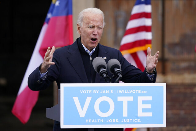 FILE - In this Tuesday, Dec. 15, 2020, file photo, President-elect Joe Biden speaks at a drive-in rally for Georgia Democratic candidates for U.S. Senate Raphael Warnock and Jon Ossoff, in Atlanta. The first full week of 2021 is shaping up to be one of the biggest of Biden's presidency. And he hasn't even taken office yet. (AP Photo/Patrick Semansky, File)