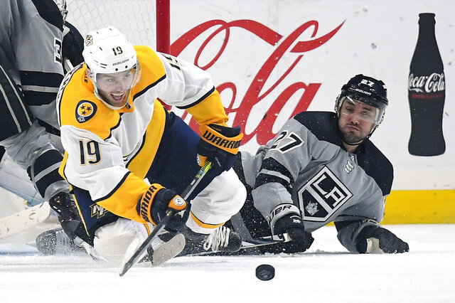 Nashville Predators center Calle Jarnkrok, left, passes the puck as he and Los Angeles Kings defenseman Alec Martinez fall to the ice during the second period of an NHL hockey game Saturday, Jan. 4, 2020, in Los Angeles. (AP Photo/Mark J. Terrill)