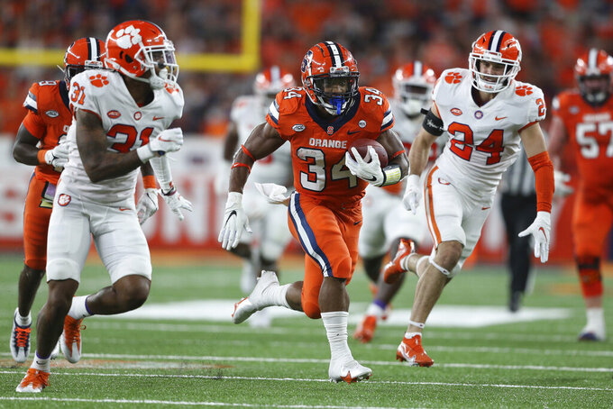 Syracuse running back Sean Tucker (34) rushes during the second quarter of the team's NCAA football game against Clemson in Syracuse, N.Y., Friday, Oct. 15, 2021. (AP Photo/Joshua Bessex)
